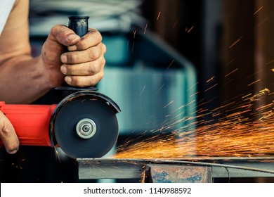 worker grinding or cutting metal with grinder. close up shot. a lot of sparks while grinding iron. with copy space.