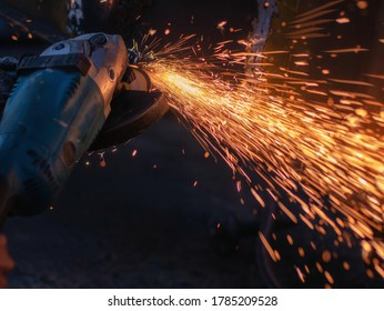 worker grinding cutting metal sheet with grinder machine overwrites the master of welding seams angle grinder and sparks. Electric grinder in the industrial workshop.