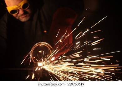 Worker grinding iron metal