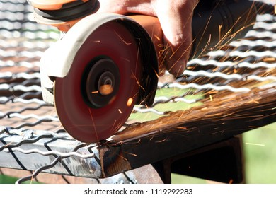 Worker grinding  a metal part without standard protection equipment