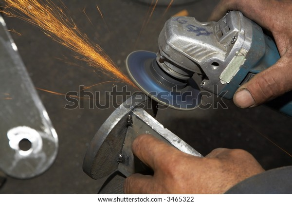 worker grinding steel and sparks