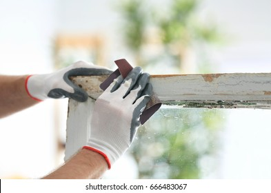 Worker grinding surface of old window frame with abrasive paper, closeup