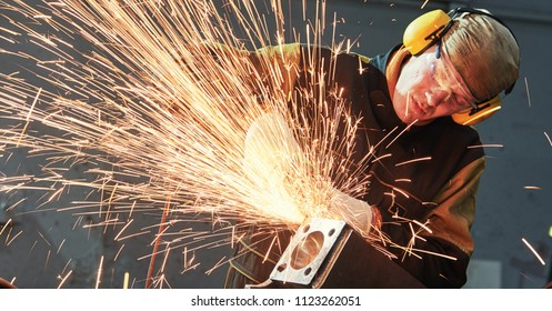 worker grinding weld seam with grinder machine and sparks