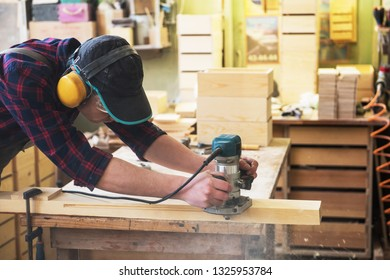 Worker grinds the wood box of angular grinding machine. Profession, carpentry and woodwork concept.