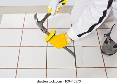 Worker with hammer removes old white tiles from floor