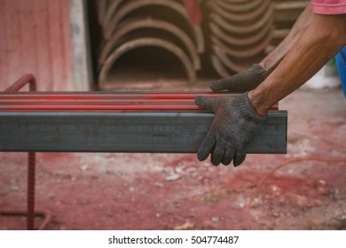 worker hand hold steel for spraying red color to the steel .