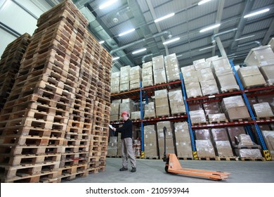 worker with hand pallet truck preparing delivery - stack of wooden pallets in storehouse