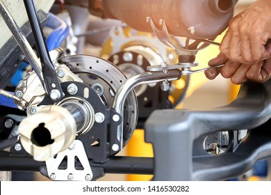 Worker hand tightening or loosening a nut of a bolt with a wrench for automotives part.