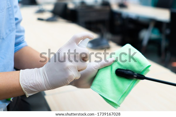 worker hand wearing gloves using disinfectant spray and cloth to clean microphone in conference room to prevent covid-19 or coronavirus infection. new normal and social distancing concept