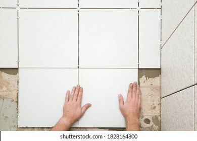 Worker hands gluing white ceramic tiles on floor. Closeup. Point of view shot.