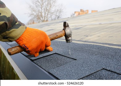 Worker hands installing bitumen roof shingles using hammer in nails.