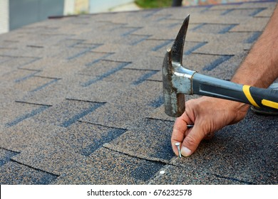 Worker hands installing bitumen roof shingles with hammer and nails.