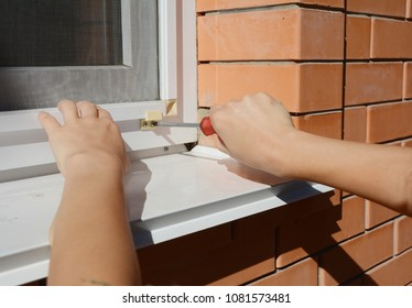 Worker hands installing mosquito net,  mosquito wire screen on  house window.