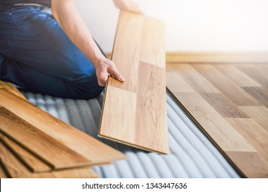 Worker hands installing timber laminate floor. Wooden floors house renovation with measure items.