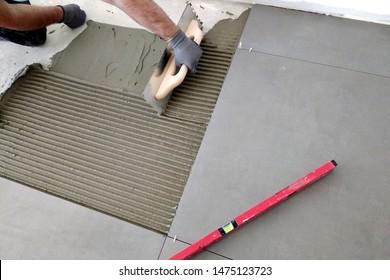 Worker hands putting ceramic tiles on the floorl.