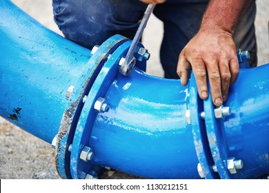 Worker hands screwing nuts on new drink water piping - close up