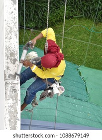 A worker hanging from the top of building inject silicone rubber to repair building's cracks before repainting color process