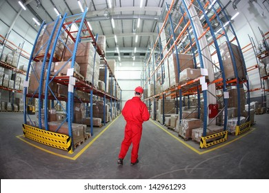Worker in hard hat and red uniform in warehouse - back view