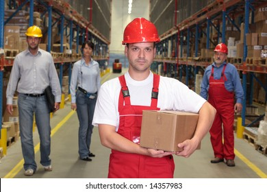 worker in hardhat with parcel at the front of team of workforce in warehouse