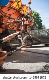 Worker heats a hose for supplying hot bitumen emulsion and crushed stone for repairing the road surface