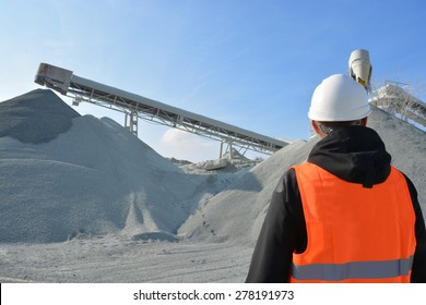 Worker and heavy machine for gravel production in background