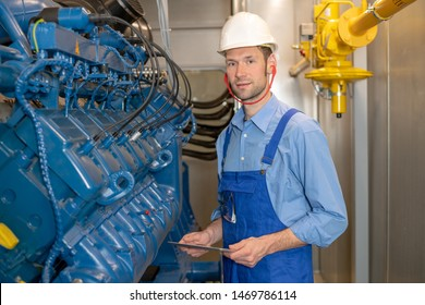 worker with helmet and clipboard working on big generator