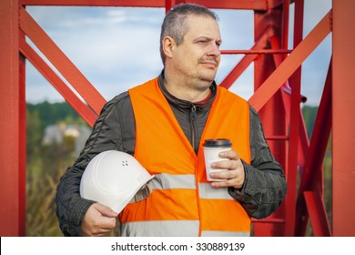 Worker with helmet and coffee  at outdoor
