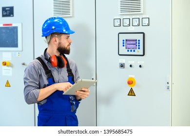 worker with helmet ,ear protector and tablet computer in industrial plant