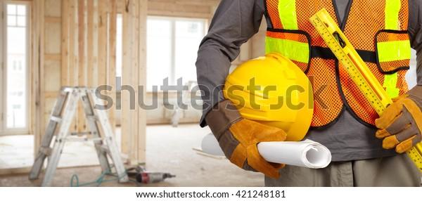 Trabajador con casco en chaleco de seguridad naranja.