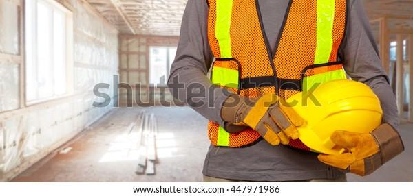 Worker with helmet in orange security vest.