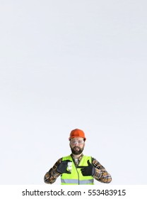 Worker in a helmet and protective clothing with a light bulb in his hands on grey background