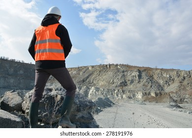 Worker in a helmet and quarry in background