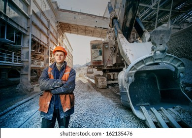 worker in a helmet stands near a big excavator crossed arms