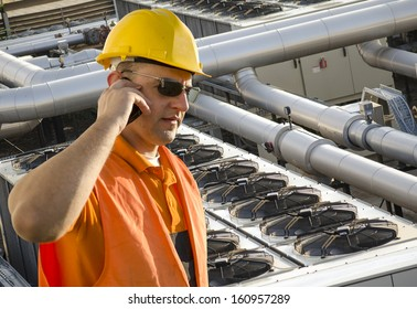 worker with helmet and sunglasses talking on mobile phone in front of cooling plant