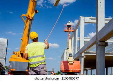 Worker is helping crane from the ground, keep balance and direction. Rigger is helping mobile crane with rope to manage concrete joist for assembly huge construction.