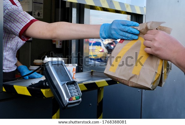 McDonald's worker holding bag of fast food. Hand trough the window of mcdonalds car mcauto. Window for payment and issuing an order in mcauto. Russia Moscow 1.07.2020