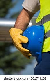 worker holding blue helmet