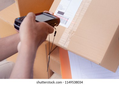 Worker holding a bluetooth bar code scanner with scanning on a package box.
