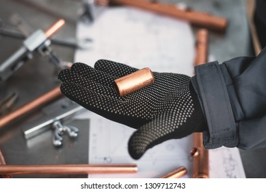 Worker is holding in hands a brass pipe trimming on a fitter workbench background. Pipework.