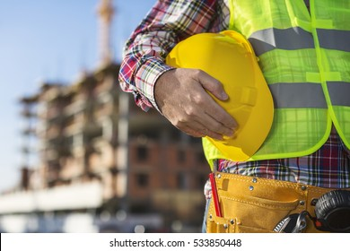 Worker holding hard hat close up shot