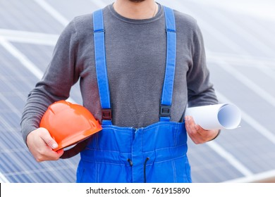 Worker holding a hard hat and curled project in his hands against the background of solar panels