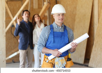 Worker holding house design plans and a young couple at construction site
