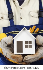 Worker holding house model in hand. Real property or insurance concept