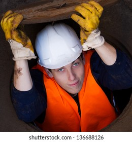 Worker holding manhole cover on top of his head while being half way inside the manhole / Down The Manhole