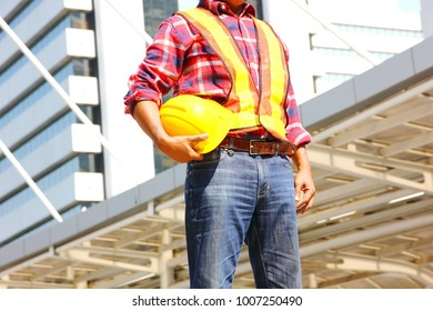 the worker holding safty hat in his hand at at construction site,safty equipment