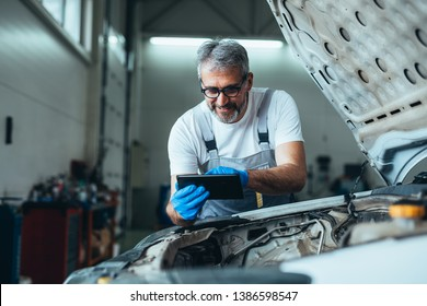 worker holding tablet in car service