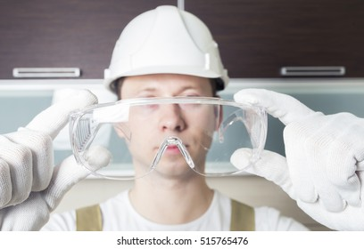 Worker holding transparent safety glasses. Head wearing white hard hat.