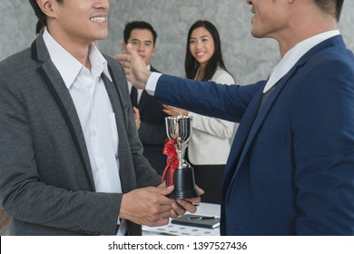 Worker holding trophy prize for best employees of the month in his hand. People in team celebrating as background.