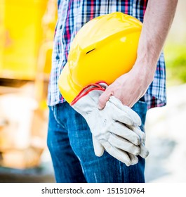 worker holding yellow helmet and gloves