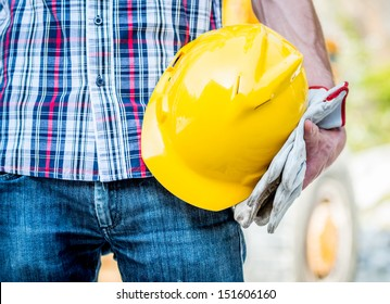 worker holding yellow helmet and gloves close up